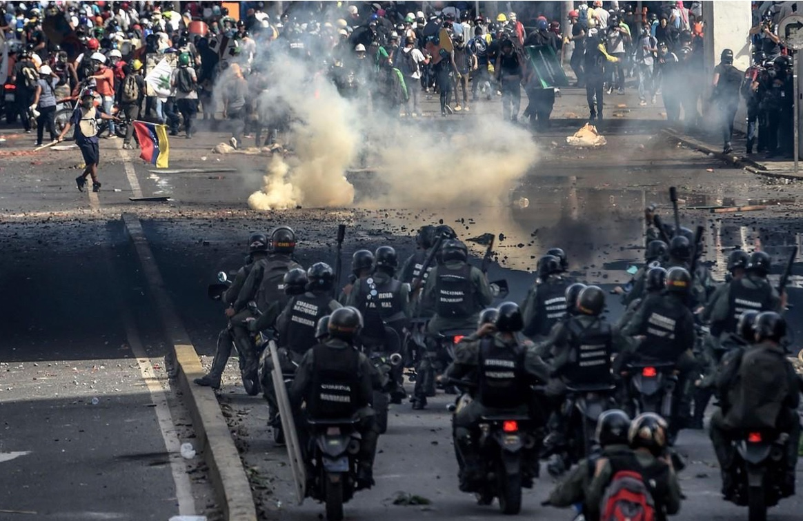 Riot police officers confront opposition activists